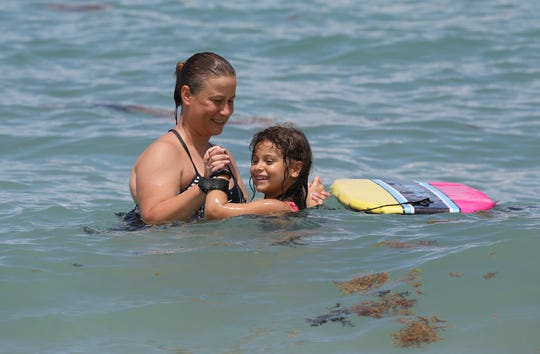Shark attack victim Violet Jalil (right), 5, and her mother Jessica Veatch, both of Port St. Lucie, swim in the ocean at Waveland Beach on Hutchinson Island in St. Lucie County, on Wednesday, July 17, 2019, just north of Jensen Beach. Violet was attacked by a bull shark, bitten on her right leg almost two years ago at Bathtub Beach in Stuart, and returned to the beach for the first time to play and swim in the water.