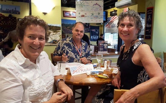 Helping People Succeed Board Chair Bliss Browne, left, with artists Dan Mackin and Jeanne Mackin at Taste Casual Dining for White Shirt Night.