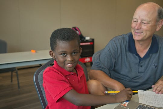 Rick McCarthy, right, a volunteer tutor with Miss B's Learning Bee's, works with Damien on a weekly basis. McCarthy also is chairman of the board of Miss B's Learning Bee's.