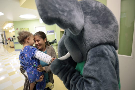 Leonel Solis, 2, and his mother, Rosa Solis, smile as Leonel plays with an El Paso Zoo mascot in the halls of the El Paso Children's Hospital on Wednesday, July 17, 2019.