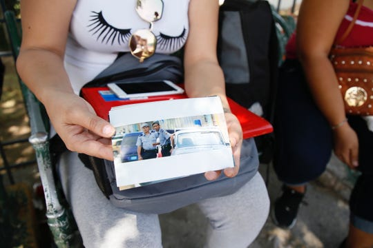'Beatriz,' 26, holds a photo of Cuban police allegedly watching her. The Cuban national, who asked for her name to be withheld for her safety, said police forced their way into her home and assaulted her. She is among the thousands waiting in Juarez to request asylum in the United States.