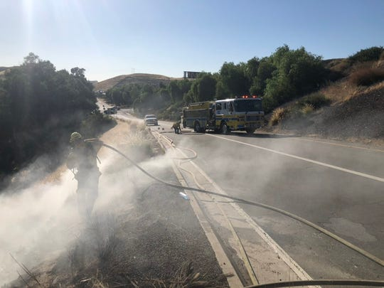 Firefighters work on a small brush fire on Kuehner Drive at Highway 118 in Simi Valley Tuesday evening.