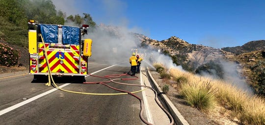 Firefighters work on a small brush fire along the Kuehner Drive onramp to Highway 118 in Simi Valley Tuesday evening.