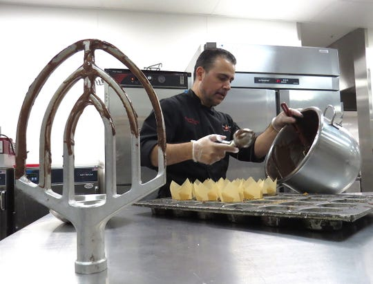 Pastry chef Sergio Gonzalez uses an ice cream scoop to transfer cupcake batter to a parchment paper-lined baking pan in the kitchen at CSU Channel Islands in Camarillo.