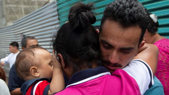 A Guatemalan migrant, who was deported from the United States, embraces relatives after arriving at the air force base in Guatemala City on Tuesday. That was the day the Trump administration planned to launch a drastic policy change designed to end asylum protections for most migrants who travel through another country to reach the United States.