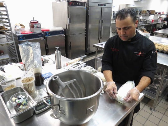 Sergio Gonzalez, pastry chef for University Auxiliary Services at CSU Channel Islands in Camarillo, gets ready to turn a 4-pound block of cream cheese into frosting for cupcakes.