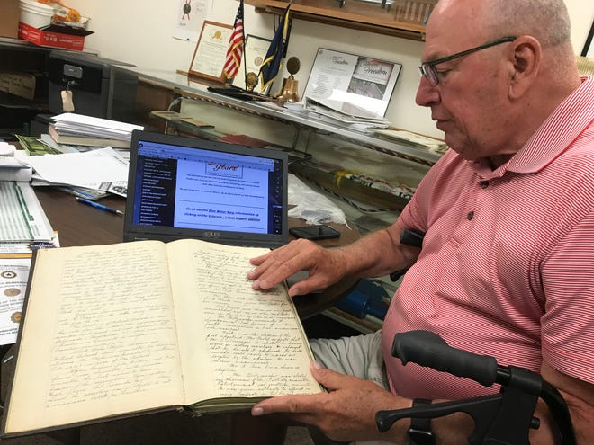 Bob Weller, vice commander of Wausau's American Legion Montgomery Plant Dudley Post No. 10, displays some of the minutes from meetings held in shortly after World War I which helped establish the post.