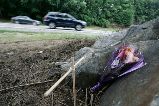Motorists traveling northbound on the Taconic State Parkway pass a wooden cross and flowers that appear to have been left July 29, 2009 at the scene of Sunday's fatal accident. Diane Schuler drove the wrong way on the parkway and collided with another vehicle, killing her daughter, three nieces and four adults, including herself.