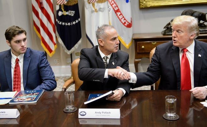 J.T. Lewis, brother of Sandy Hook mass shooting victim Jesse Lewis, watches as Andy Pollack, father of Parkland shooting victim Meadow Pollack, and President Donald Trump shake hands during a round-table discussion about school safety on Dec. 18, 2018.