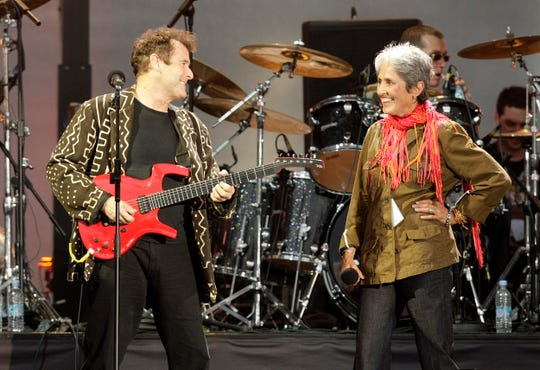 South African musician Johnny Clegg, left, is seen performing with singer Joan Baez at a 2008 London concert celebrating the 90th birthday of Nelson Mandela.