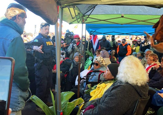 Officers from the Hawaii Department of Land and Natural Resources prepare to arrest protesters, many of them elderly, who are blocking a road to prevent construction of a giant telescope on a mountain that some Native Hawaiians consider sacred.