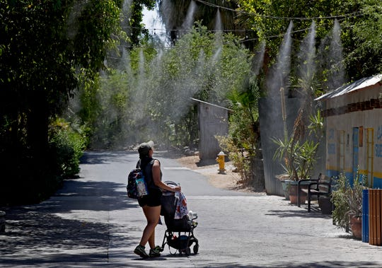 Visitors keep cool under misters at the Phoenix Zoo on July 16, 2019, in Phoenix.
