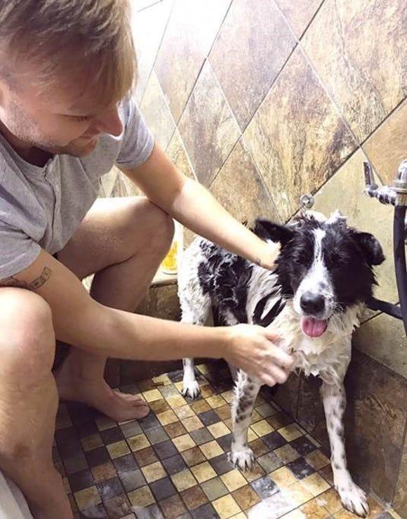 Austin gives his dog, Andy, a bath.