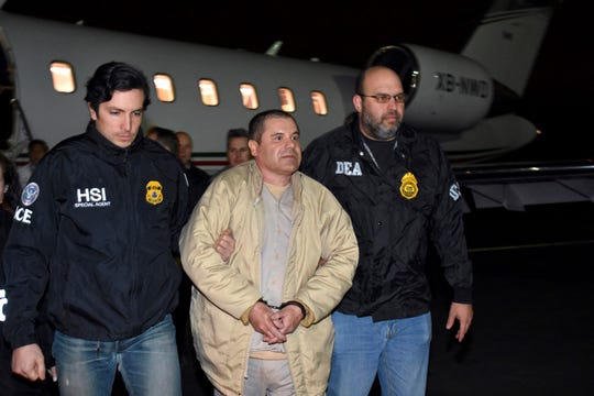 """Authorities escort Joaquin """"El Chapo"""" Guzman from a plane to a waiting caravan of SUVs at Long Island MacArthur Airport, in Ronkonkoma, N.Y. Guzman, who was convicted in February 2019 on multiple conspiracy counts in an epic drug-trafficking case, will be sentenced in a New York courtroom on July 17, 2019."""