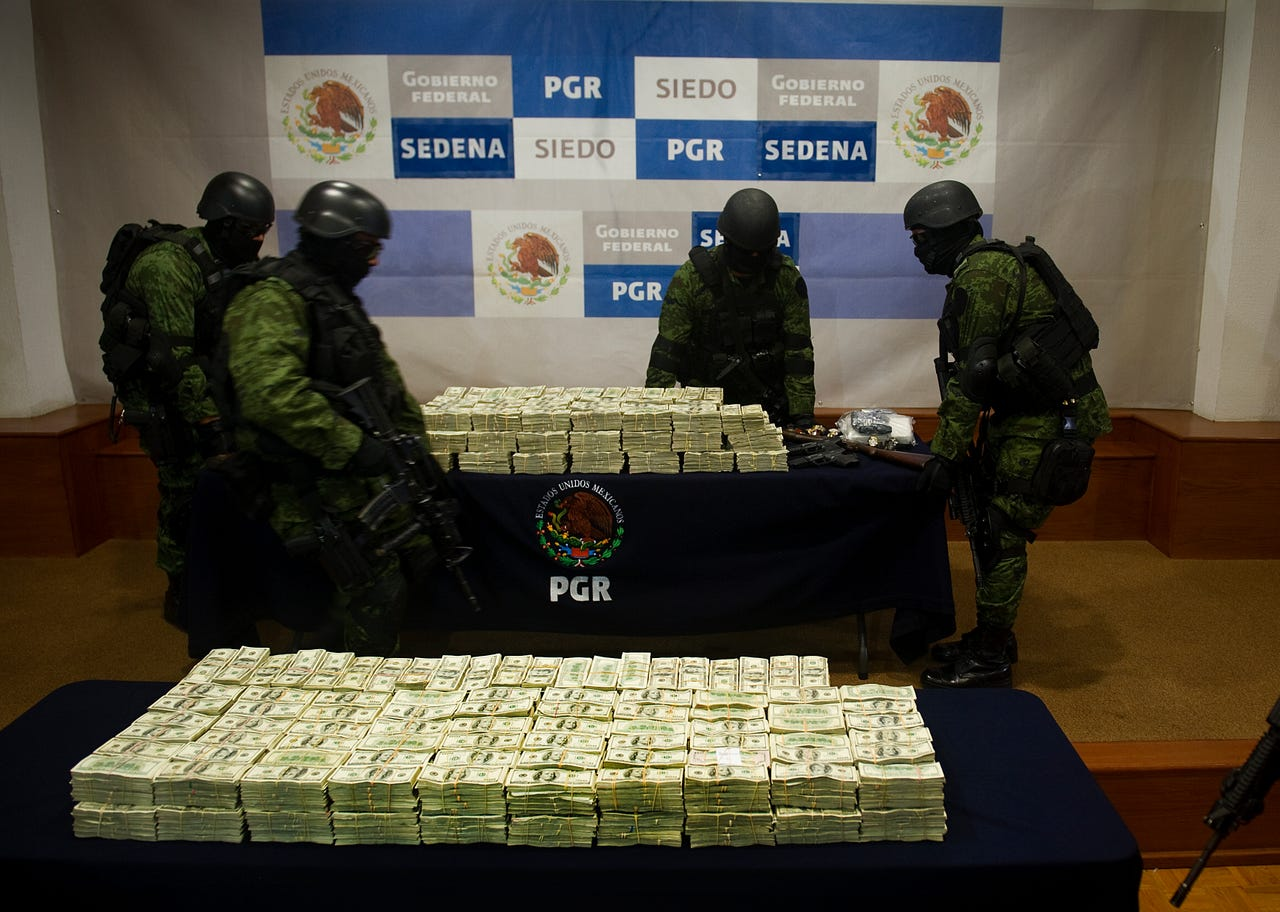 Mexican army soldiers hold a table with part of more than 15 million US dollars after a presentation to the press on November 22, 2011 in Mexico City. The money was sized to alleged members of the Guzman Loera drug cartel, led by Joaquin