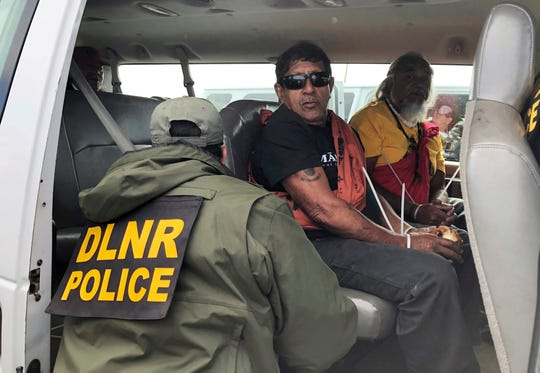 Officers from the Hawaii Department of Land and Natural Resources arrest protesters, many of them elderly, who are blocking a road to prevent construction of a giant telescope on a mountain that some Native Hawaiians consider sacred.