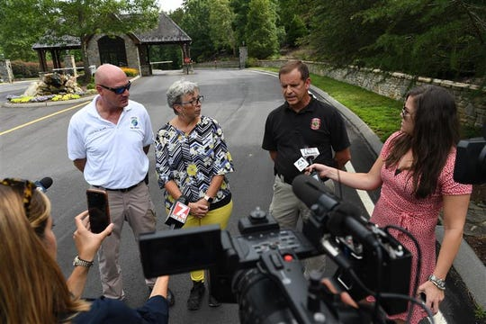From left, fire chief Phillip Black of vineyards fire district, Kandy Kelley, Pickens County Coroner, and Scott Smith, director of Pickens County Emergency services, talk to media after a house collapsed on July 18, 2019. The house collapse resulted in the death of two people.