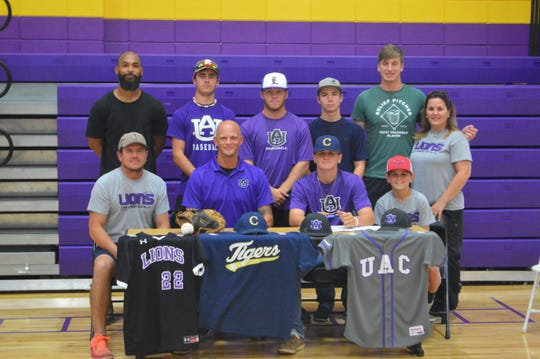 University Academy's Robert Cormier (front, second from right) signed with Champion Christian College Tuesday.