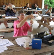 New volunteers with HRWC's water quality monitoring program, Suzie Adelmann, Larry Bundy and Doug Calkins, learn how to test the dissolved oxygen content in the water at a 2012 Adopt-A-Stream workshop.