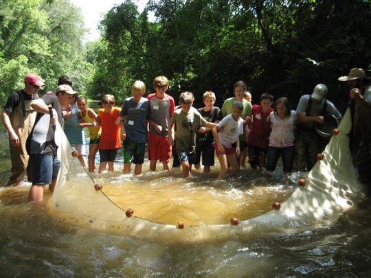 With support from N.C. Wildlife Resources Commission staff, kids use a seine to sample the fish community of Brasstown Creek during one of HRWC's Creative & Recreational Environmental Education for Kids summer day camps.