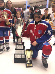 Chenango Valley fifth-grader Robbie Matson poses with the trophy after helping the Connecticut Junior Rangers to the Brick International Hockey Tournament title July 7 at Edmonton, Alberta.