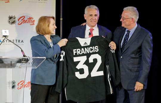 Ron Francis, center, is presented with a hockey jersey by Seattle Mayor Jenny Durkan, left, as Seattle Hockey Partners CEO Tod Leiweke looks on Thursday, July 18, 2019, in Seattle, as Francis is introduced as the first general manager for Seattle's yet-to-be-named NHL expansion team. Francis, a Hall of Famer and a two-time Stanley Cup winner, will have complete control of operations under Leiweke when the team debuts in 2021.