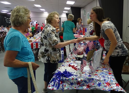 Mindy Brewer of American Nursing Care, right, greets Ellen Johnson of Bucyrus during the Senior Citizens Day event in the Youth Building of the Crawford County Fair on Thursday.