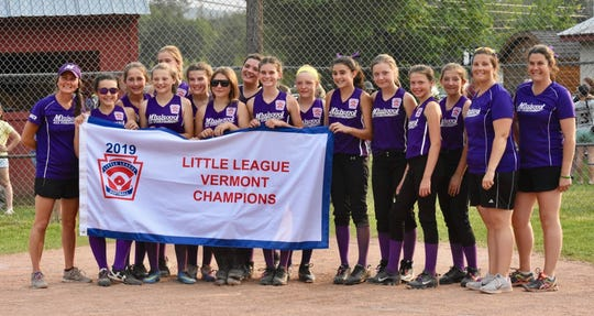 The 11- and 12-year-old Missisquoi all-stars pose with the state banner after winning the Little League softball championship last week. The group advances to regionals in Bristol, Connecticut.