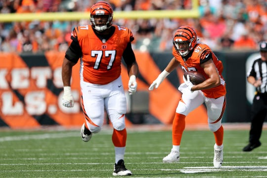 Cincinnati Bengals tight end C.J. Uzomah (87) looks for running room after catching a pass as Cincinnati Bengals offensive tackle Cordy Glenn (77) blocks in the first quarter during the Week 5 NFL game between the Miami Dolphins and the Cincinnati Bengals, Sunday, Oct. 7, 2018, at Paul Brown Stadium in Cincinnati.