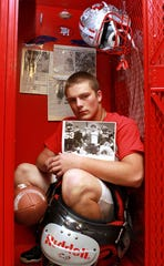 On Nov. 4, 2010, then-Dixie Heights senior Brian Pillman Jr. poses with his photos and one photo by Marilyn Shapiro from 1984 of his father Brian Pillman in his football locker at Dixie Heights High School in Edgewood, Kentucky.
