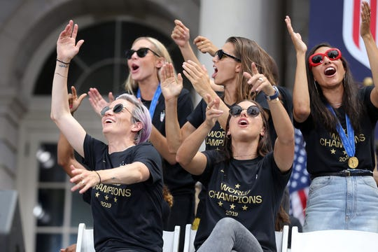 Jul 10, 2019; New York, NY, USA; United States national soccer team players (left to right) Megan Rapinoe, Allie Long, Tobin Heath, Alex Morgan and Christen Press react as forward Carli Lloyd (not pictured) speaks at New York City Hall after the ticker-tape parade for the United States women's national soccer team down the canyon of heroes in New York City.