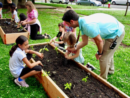 "Teacher Peter Spoganetz helping students at School No. 8 plant vegetables in their garden, which was installed on Tuesday, June 18, as part of the Union County ""Kids Dig In!"" program."