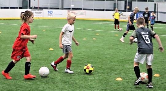 Kids practice dribbling the ball to start Wednesday's portion of the Ohio Extreme Soccer Camp at Kids America.