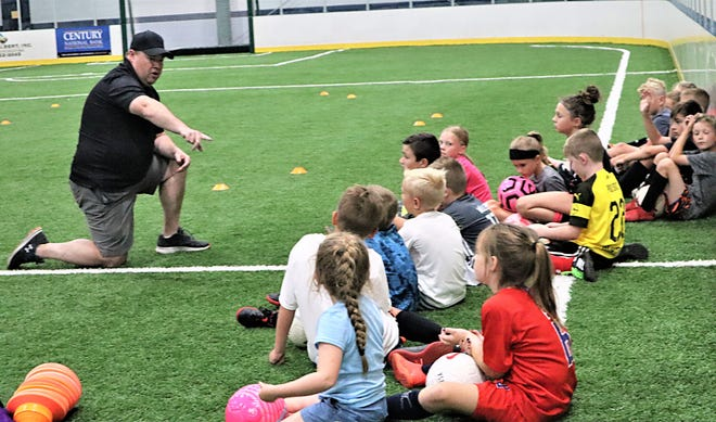 Coach Brent Ridenour gathers all of the kids at the start of practice on Wednesday during the Ohio Extreme Soccer Camp at Kids America. Around 25 kids, ages 5-14, took part in the camp this week.