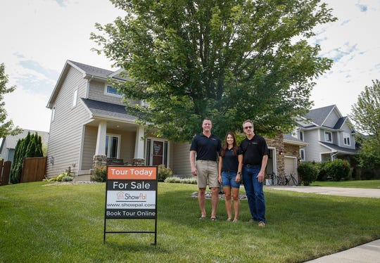 Chad and Nicole Torstenson pose with Dan Thomas, right, in front of a home they are showing via their new home sale site, ShowPal, in Waukee on Thursday, July18, 2019.