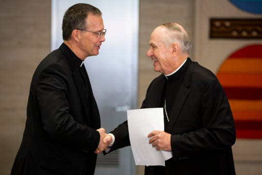 Bishop-elect Fr William Joensen of Dubuque shakes hands with Bishop Richard Pates after he is formally introduced as the successor to Pates on Thursday, July 18, 2019, in Des Moines. Joensen was born in Waterloo and will be the tenth bishop of the Des Moines Diocese.