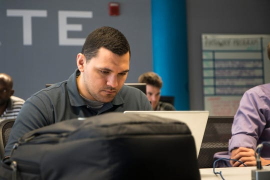 Jerry Yono, 28 of Novi attends a nine-person class at Tech Elevator, a new school teaching computer coding out of TechTown on WSU's campus in Detroit, Wednesday, July 16.