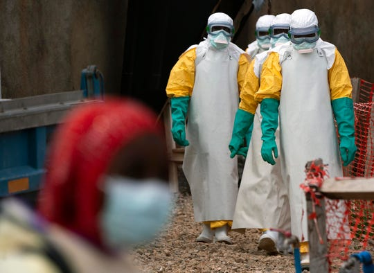 In this Tuesday, July 16, 2019 photo, health workers dressed in protective gear begin their shift at an Ebola treatment center in Beni, Congo DRC. The World Health Organization has declared the Ebola outbreak an international emergency after spreading to eastern Congo's biggest city, Goma, this week. More than 1,600 people in eastern Congo have died as the virus has spread in areas too dangerous for health teams to access.