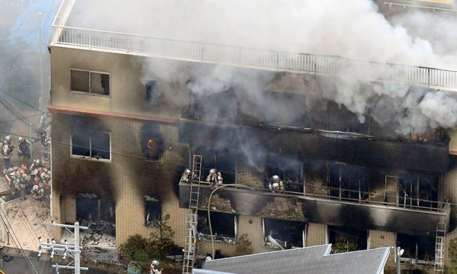 Firefighters respond to a building fire of Kyoto Animation in Kyoto, western Japan, Thursday, July 18, 2019. The fire broke out in the three-story building in Japan's ancient capital of Kyoto, after a suspect sprayed an unidentified liquid to accelerate the blaze, Kyoto prefectural police and fire department officials said.