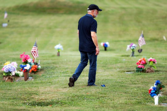 Eddie Davis walks past tributes on his way to his son Jeremy's gravestone, who died from the abuse of opioids, Wednesday, July 17, 2019, in Coalton, Ohio. Newly released prescription opioid statistics underscore how widespread pill use has been in towns and small cities of America's Appalachian region. In Jackson County, an average yearly total of 107 opioid pills for every resident were distributed over a seven-year period.