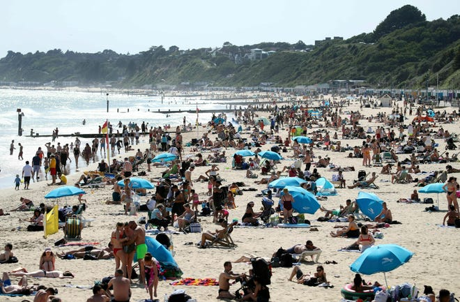 People enjoy the warm weather on Bournemouth beach in south England, Thursday June 27, 2019.
