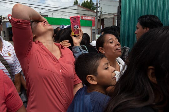 Family members wait outside the Air Force Base for the arrival of their relatives who were deported from the United States, in Guatemala City, Tuesday, July 16, 2019.