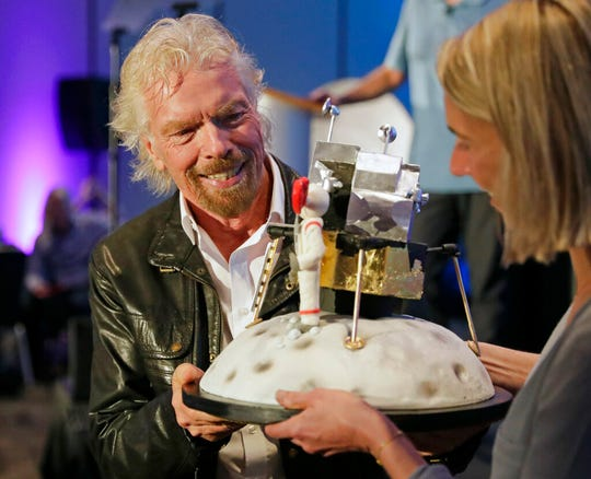 Richard Branson is presented with a space-themed cake during a luncheon attended by 100 Virgin Galactic ticket holders, to mark his 69th birthday and in recognition of the Apollo 11 moon landing anniversary at the Kennedy Space Center Visitor Complex, Thursday, July 18, 2019, in Cape Canaveral, Fla.