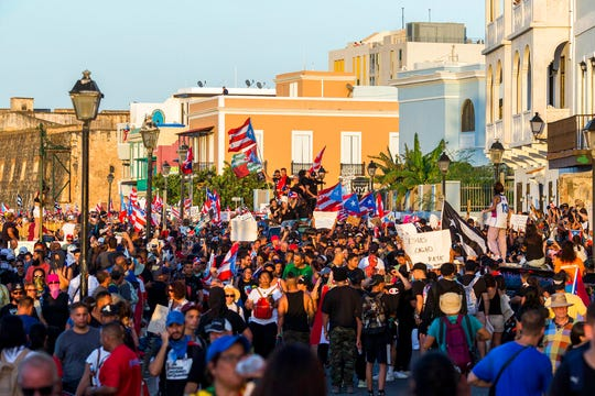 Demonstrators march against governor Ricardo Rosello, in San Juan, Puerto Rico, Wednesday, July 17, 2019. Protesters are demanding Rossello step down for his involvement in a private chat in which he used profanities to describe an ex-New York City councilwoman and a federal control board overseeing the island's finance.