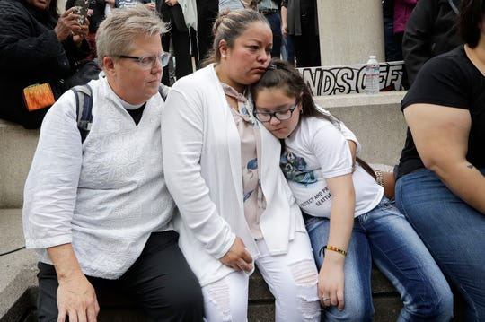 Gethsemane Lutheran Church Pastor Joanne Engquist, left, sits with Susana Robles and her daughter Natalie Robles, after their husband and father, Jose Robles, turned himself in to immigration authorities in Tukwila, Wash.