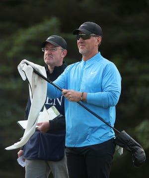 David Duval cleans one of his clubs as he waits to play the 5th tee during the first round of the British Open on Thursday.