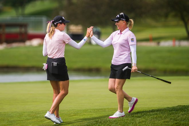 Paula Creamer, left, high-fives her playing partner Morgan Pressel as they play in the second round of the Dow Great Lakes Bay Invitational on Thursday at Midland Country Club.