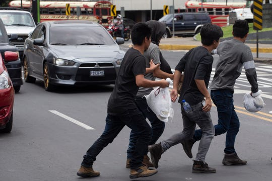 Guatemalan men who were deported from the United States, cross a street arriving in Guatemala City, Tuesday, July 16, 2019.