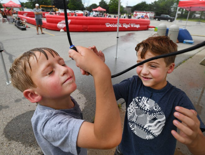 Landon Immekus, 5, and Weston Immekus, 7, of Troy, keep cool under a misting tent Thursday during a Red Wings street hockey event in the steamy parking lot of Meijer in Royal Oak.