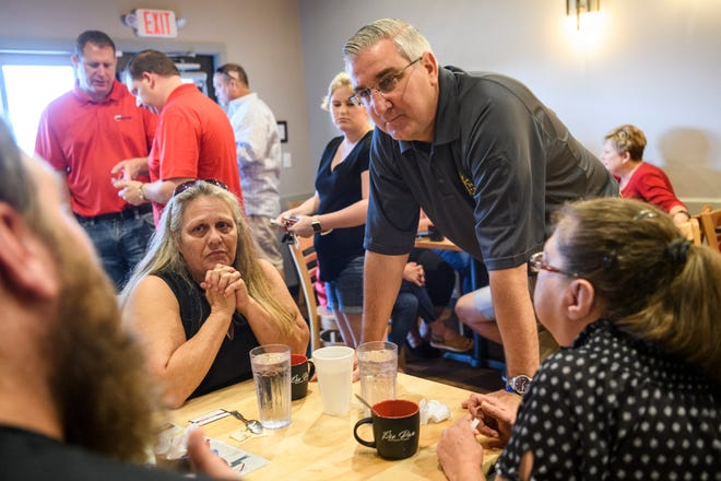 Zachary Bratcher, left, asks Gov. Eric Holcomb, center right,   a questions as Stephanie Spurlock, center left, and Robin Knipp, right, listen in during a meet-and-greet for the governor's 2020 re-election campaign at Pie Pan Restaurant & Bakery in Evansville, Ind., Thursday, July 18, 2019.